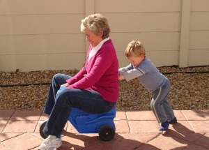 Child pushing grandmother on plastic tricycle.